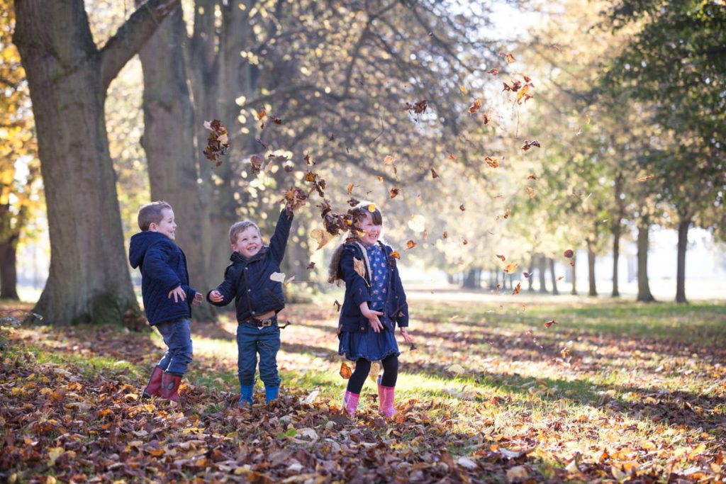 3 children playing in the autumn leaves at Coombe Abbey
