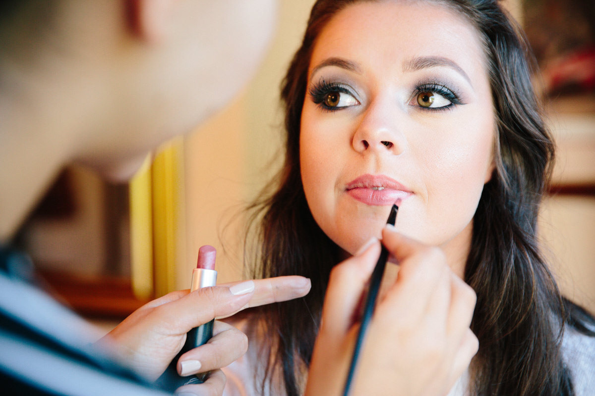 Bride having lipstick done on morning of wedding