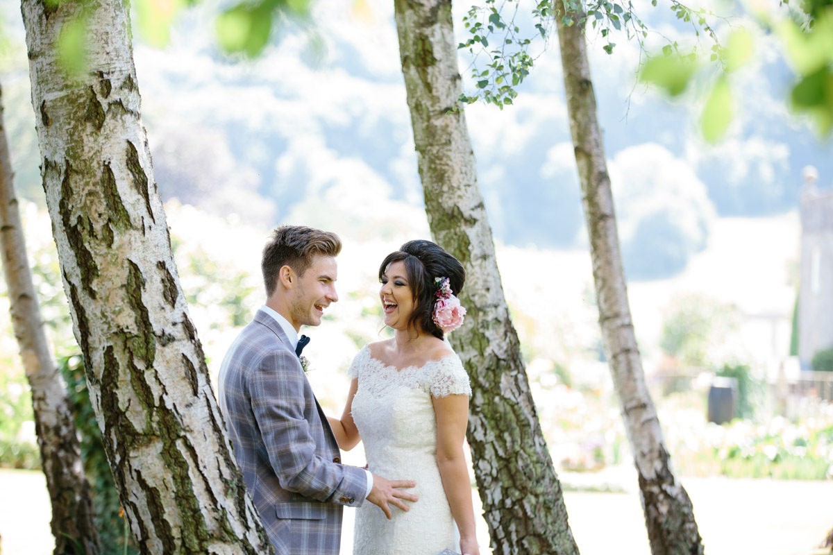 Bride and Groom standing by trees laughing
