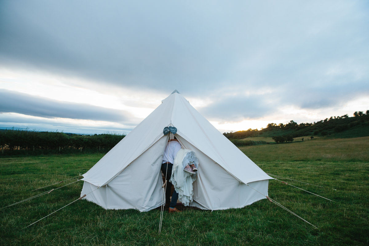 Groom carrying Bride into their wedding night tent