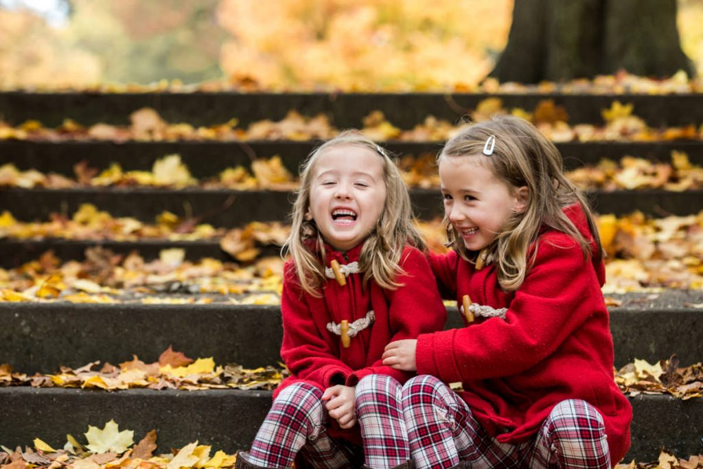two little girls sitting on stepps in autumn leaves, Jephson park Leamington Spa