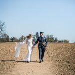 Bride and RAF groom, walking across a field