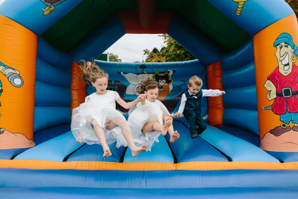 Children jumping on a bouncy castle at a wedding