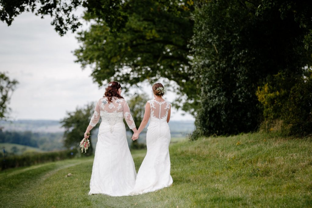 Two brides walking across a field holding hands