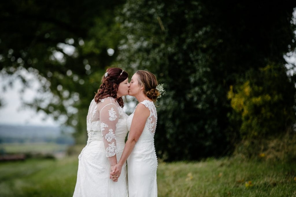 Two brides kissing in a field