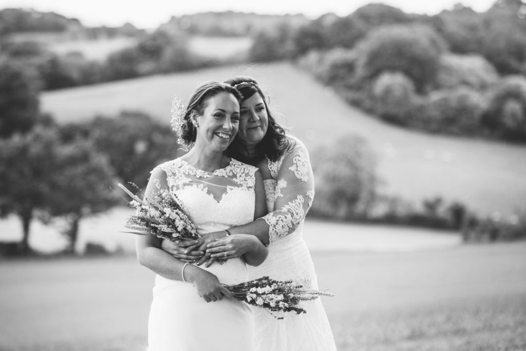 Two brides cuddling in a field