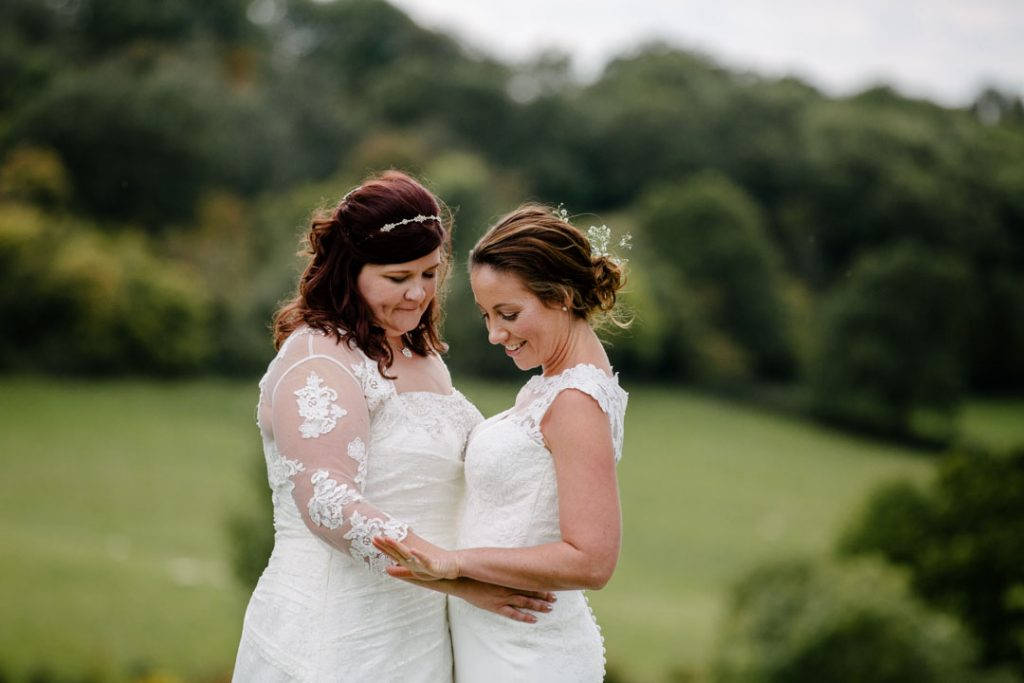 Two brides looking at their wedding ring on hand, in a field