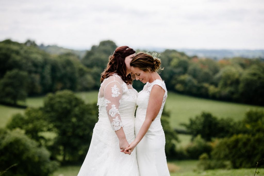Two brides sharing a tender moment in a field