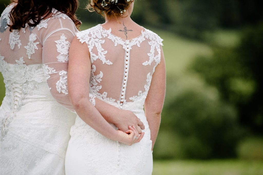 Two brides cuddling as they look out over a field