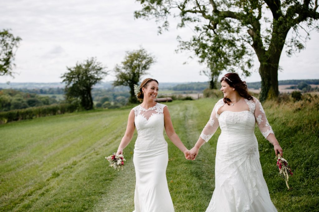 Two brides walking across a field
