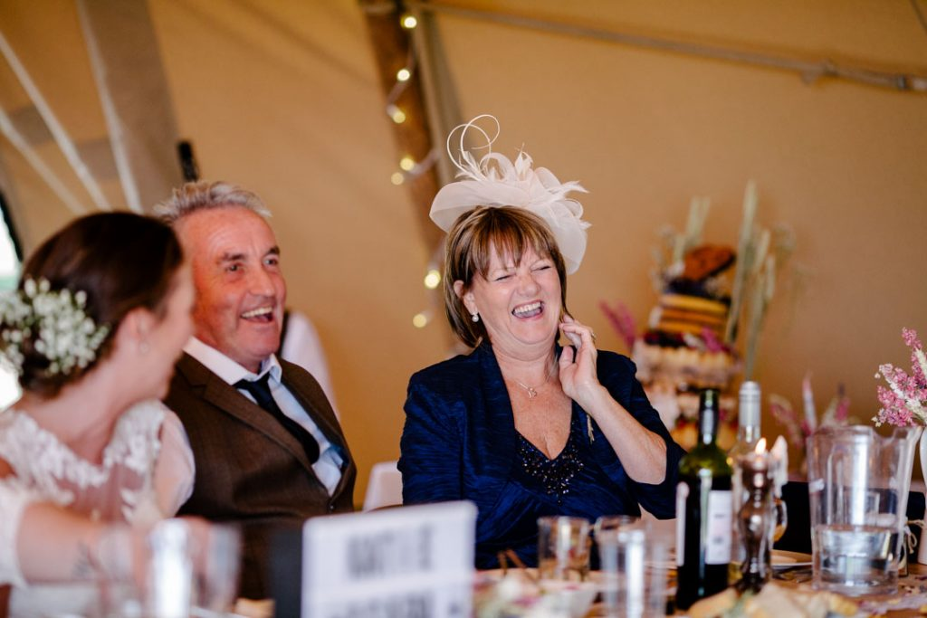 Mother of the bride laughing during speeches, tipi wedding