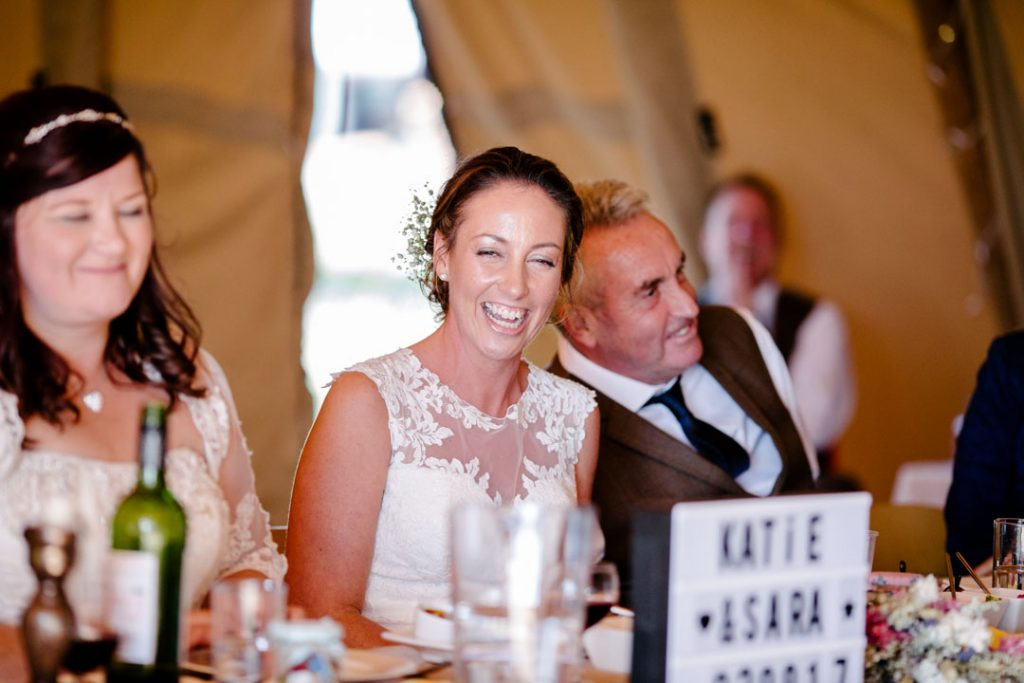 Bride laughing during speeches, tipi wedding