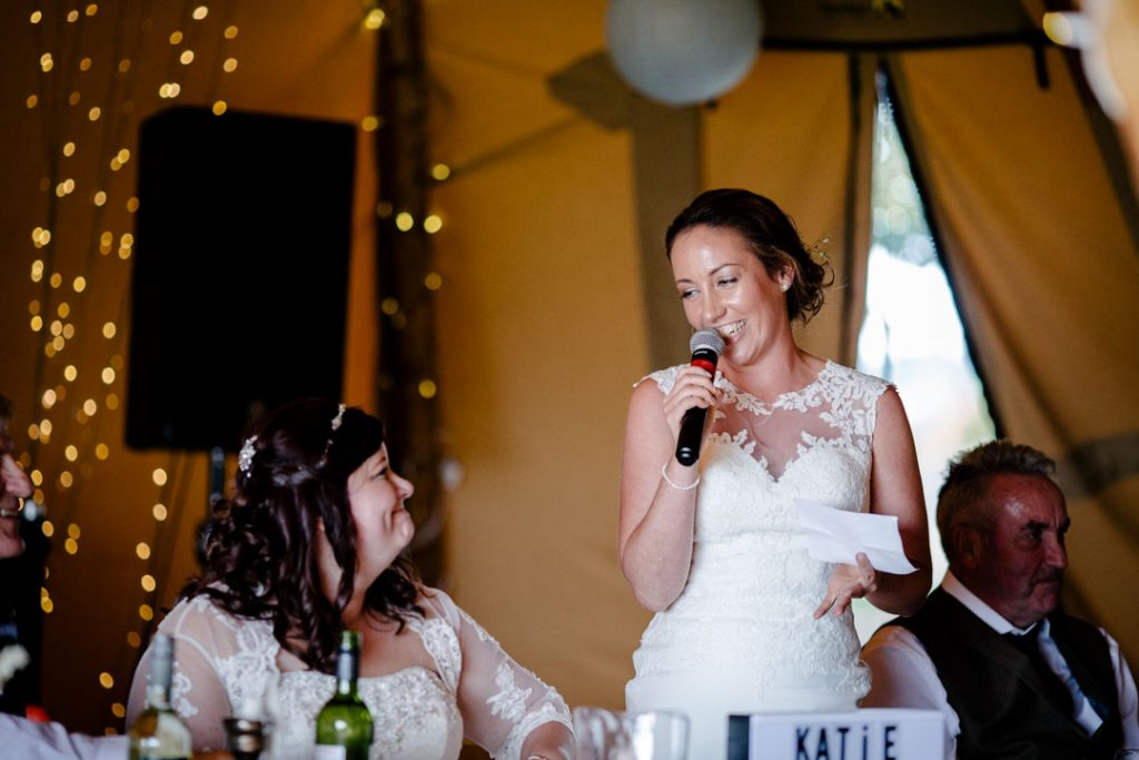 Bride giving a speech at wedding breakfast in a tipi