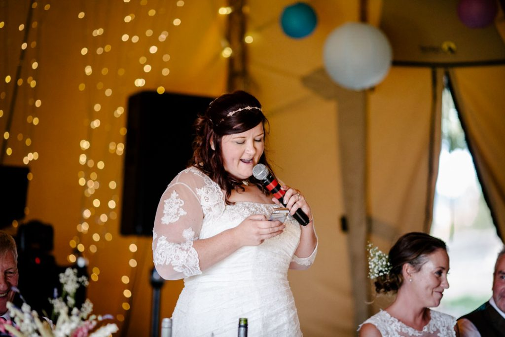 Bride giving a speech during wedding breakfast in a tipi