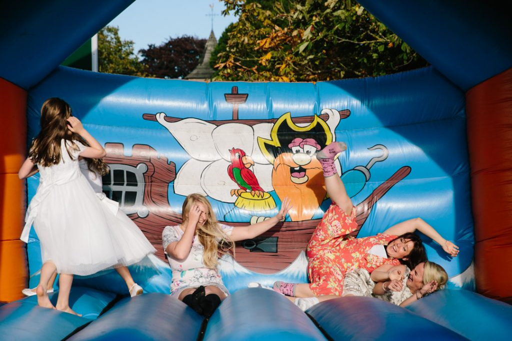 Guests falling over on a bouncy castle at a wedding