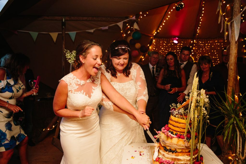 Two brides cutting a cake at their wedding in a tipi