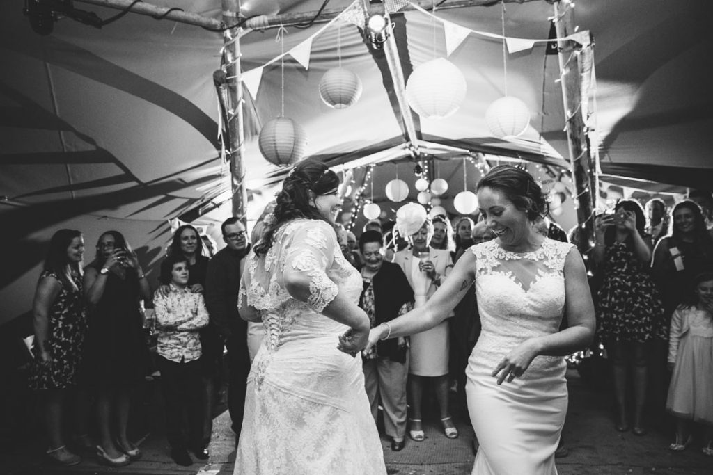 Two brides dancing their first dance at their wedding in a tipi