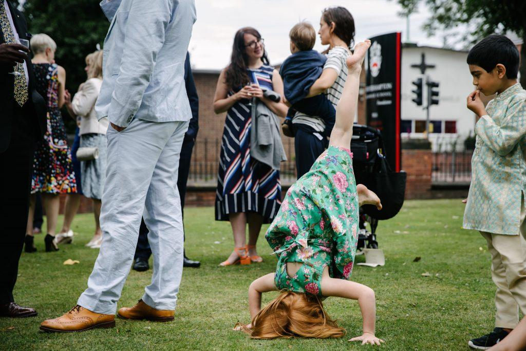 Girl doing headstand at wedding, Wolverhampton Grammar school