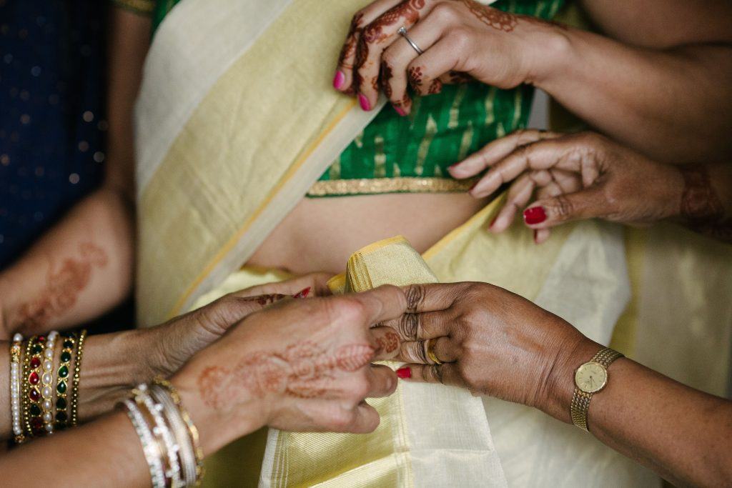 bride getting into indian wedding dress, helped by close family