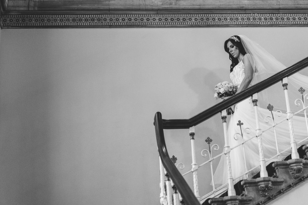 Bride walking down the stairs at Walton Hall, ready for her wedding ceremony