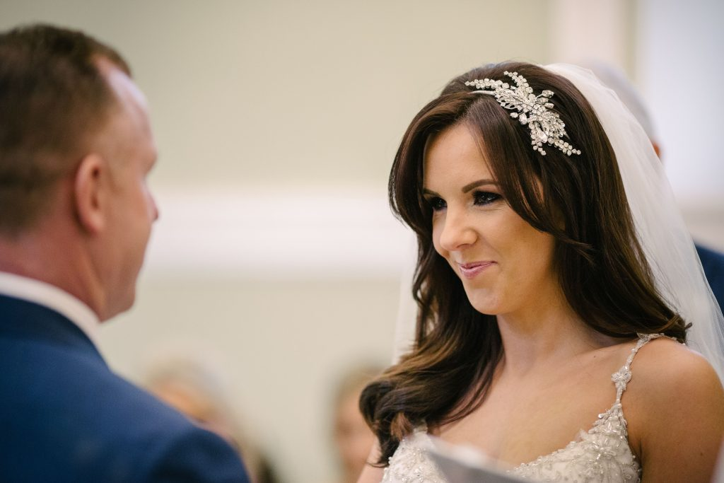Bride smiling at groom during wedding ceremony at Walton Hall