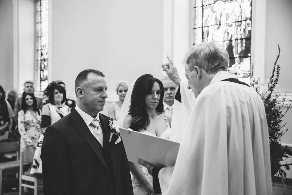 Black & white image of bride & groom during ceremony at Walton Hall