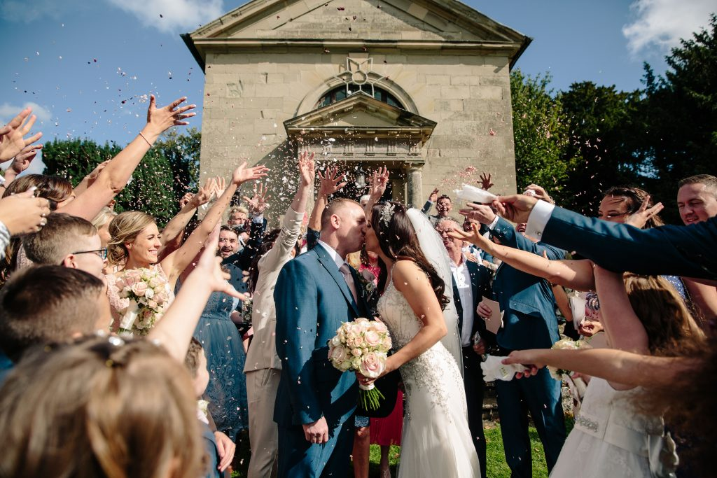 Guests throwing confetti over bride & groom outside Walton Hall