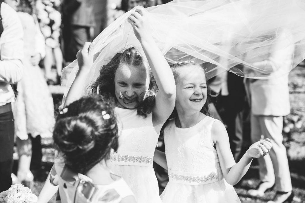 flower girls getting caught under bride's veil in the wind
