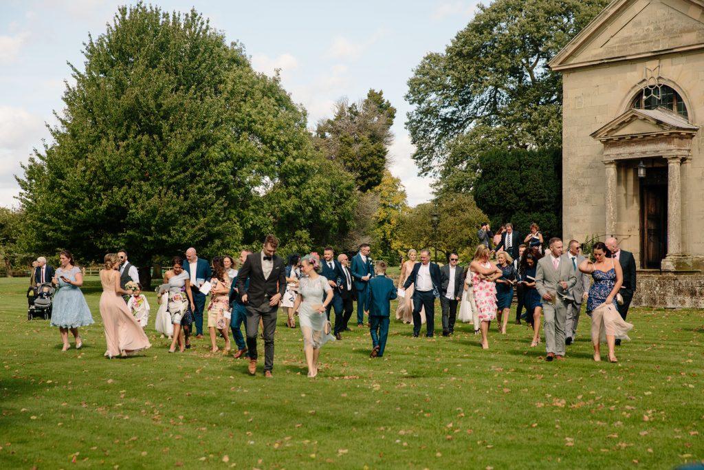 Guests walking across lawn at Walton Hall