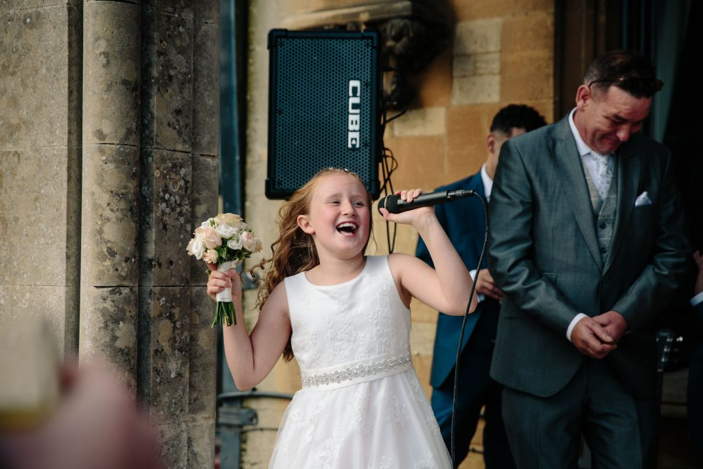Flower girl singing into microphone at wedding