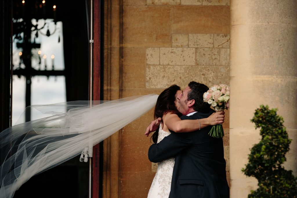 Bride hugging guest and veil blowing wildly in the wind