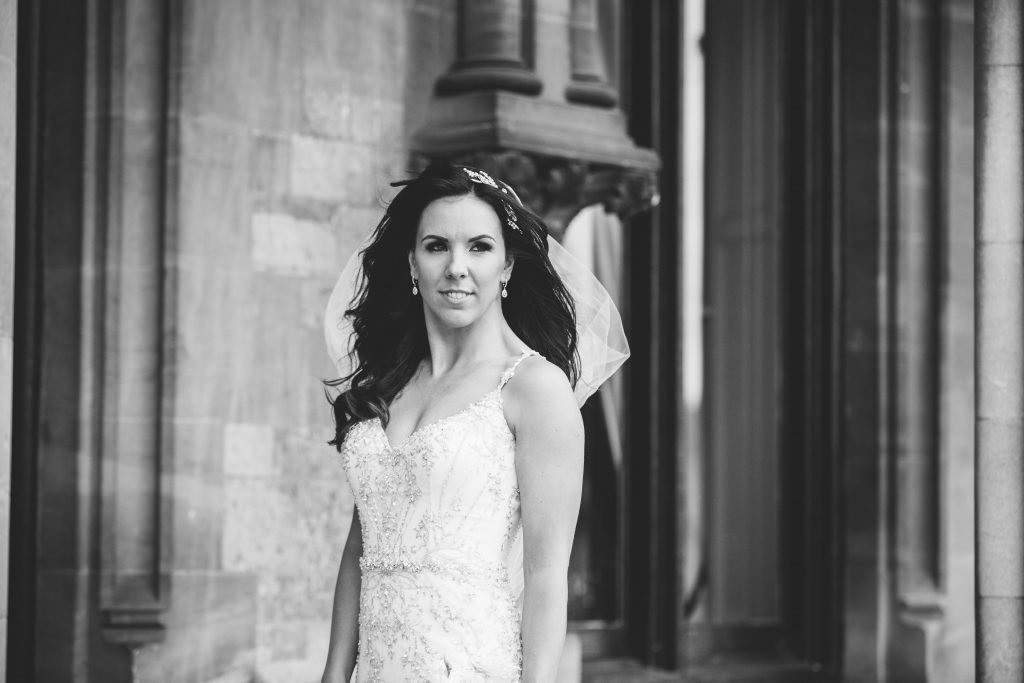 Black & white image of bride standing outside Walton Hall