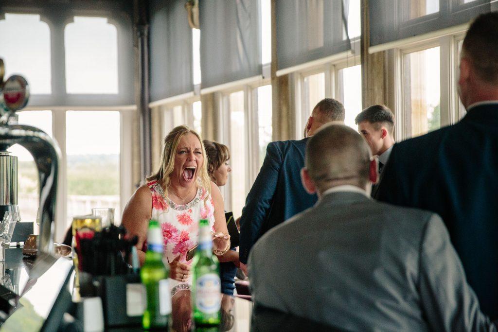 Woman at the bar at Walton Hall, laughing