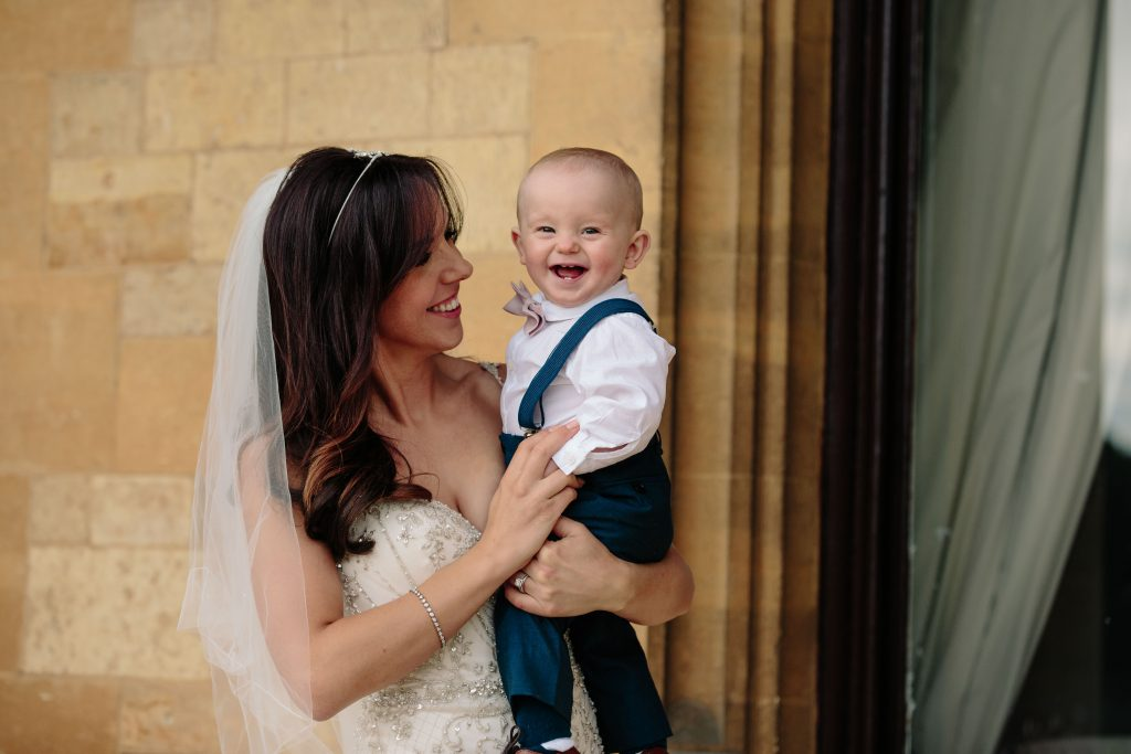 Bride holding her baby son who is laughing