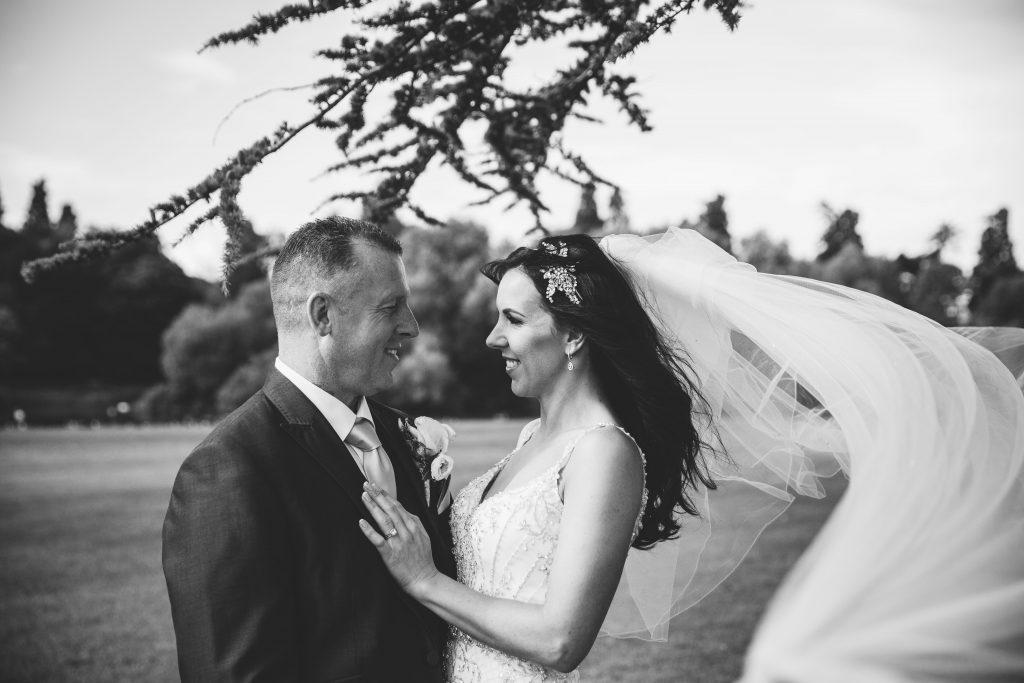 black & white image of bride & groom cuddling at Walton Hall