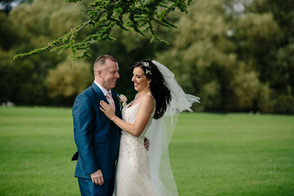 Bride and groom standing under a tree cuddling at Walton Hall