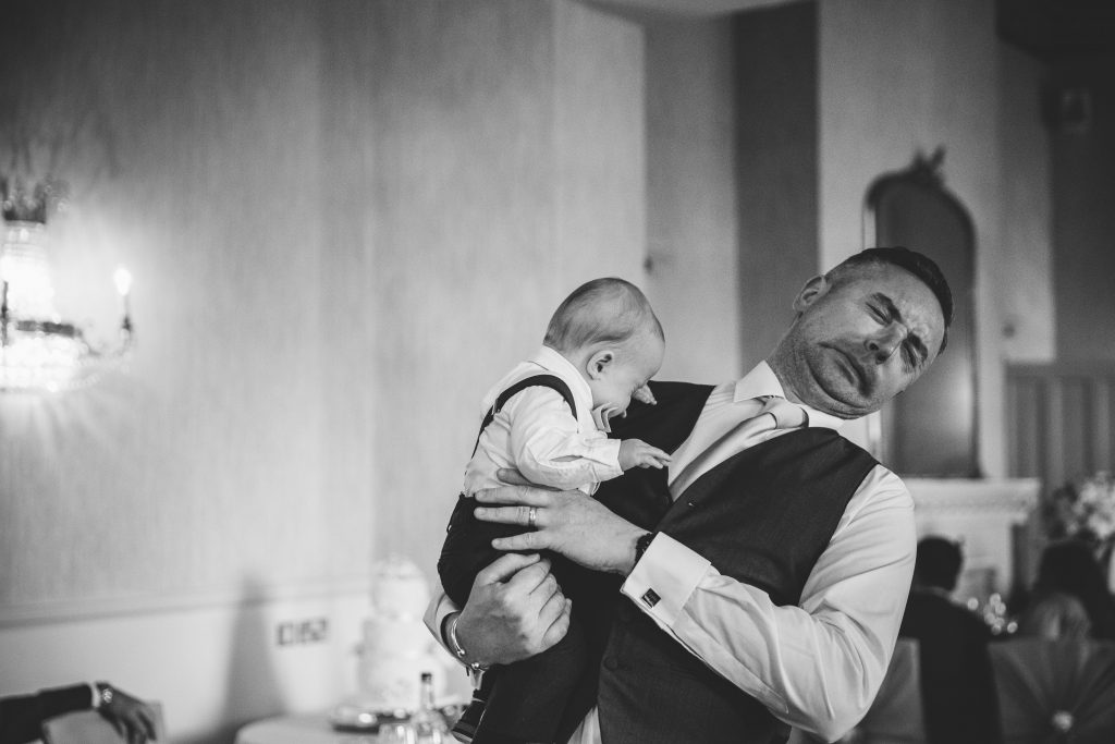black & white image of man holding a baby and pulling a face after baby sneezed