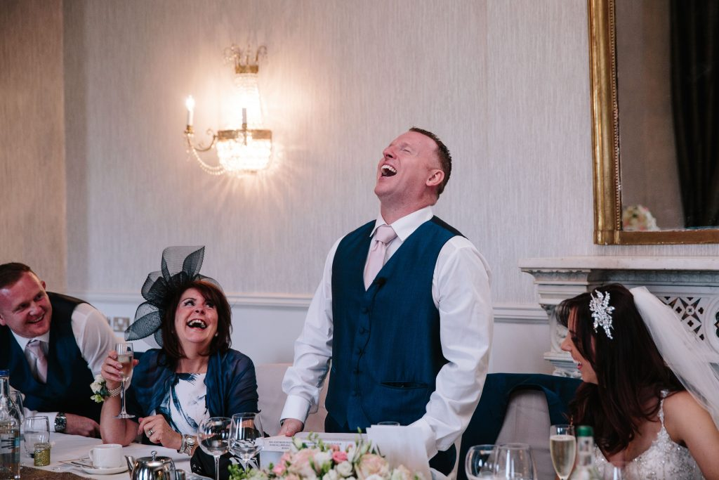 Groom laughing during his speech during wedding breakfast