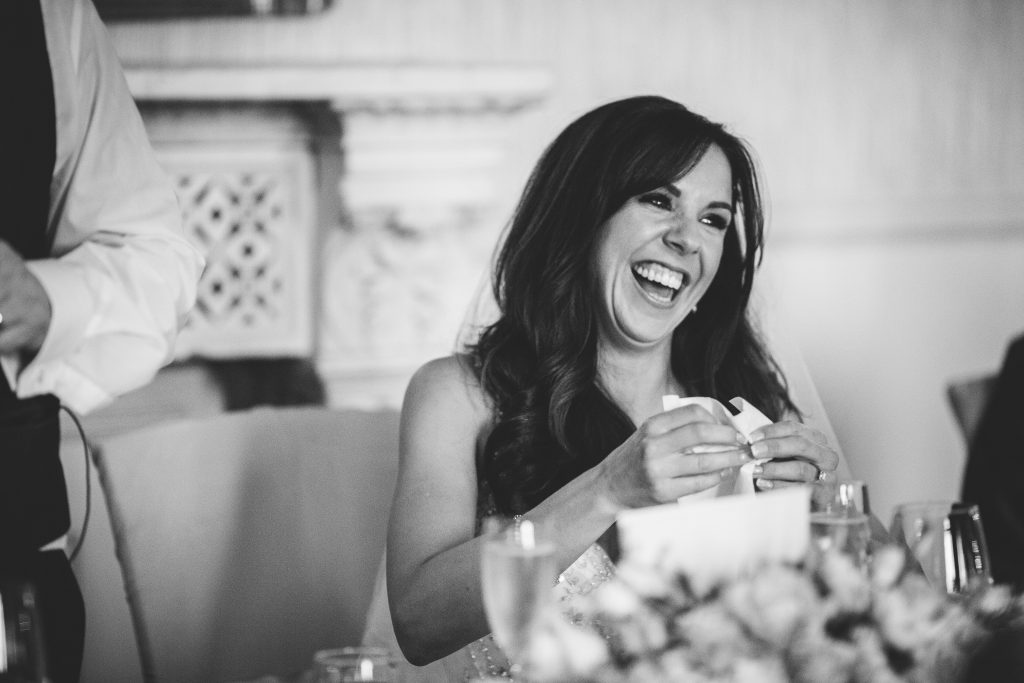 Black & white image of bride laughing during wedding speeches