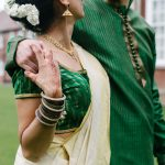 Groom walking with his arm round his bride, holding her hand which has henna tattoo on