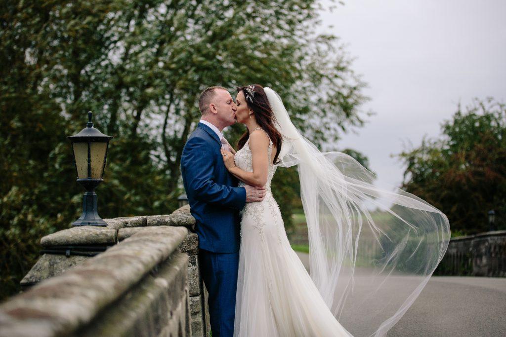 Bride & groom kissing on the bridge at Walton hall. Bride's veil is blowing in the wind