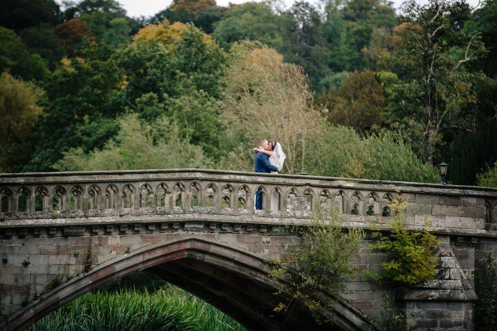 Bride & groom kissing on the bridge at Walton Hall