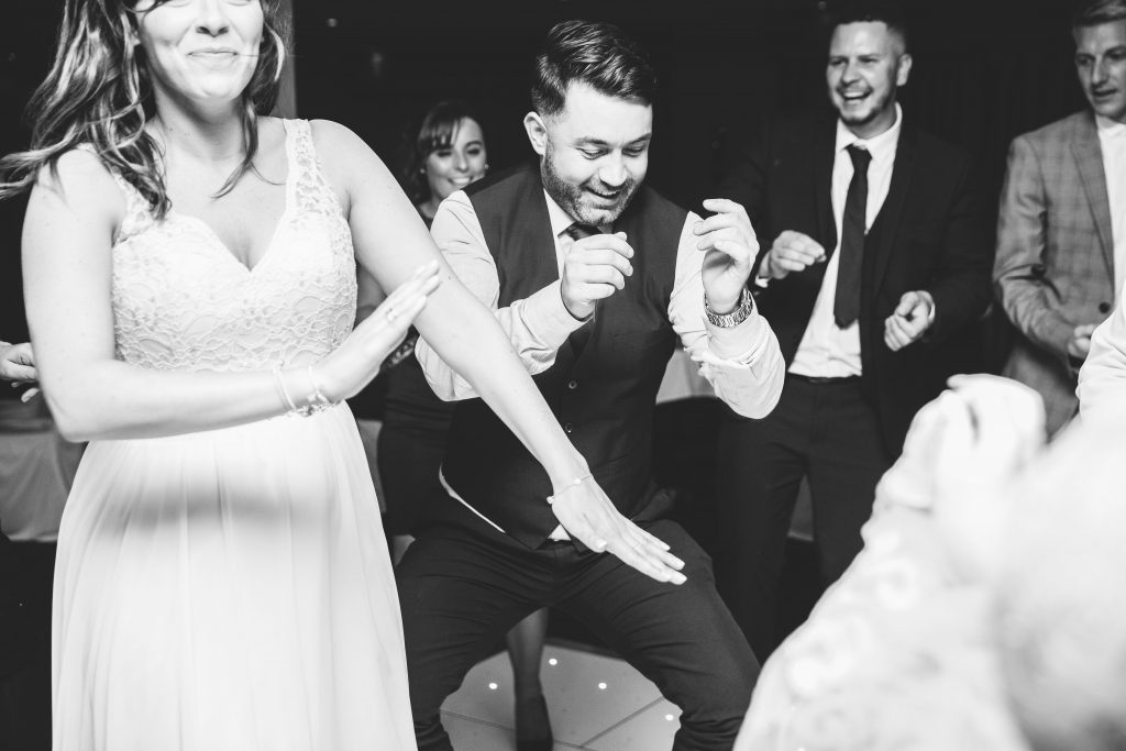 black & white image of people dancing at a wedding