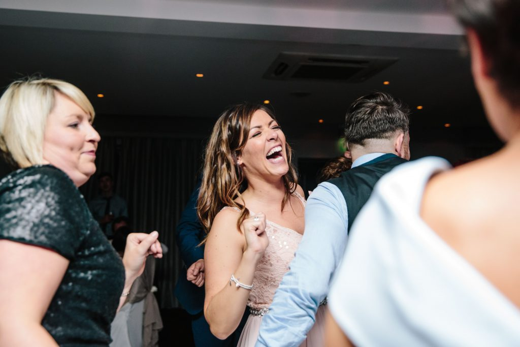 Bridesmaid laughing on dance floor at wedding