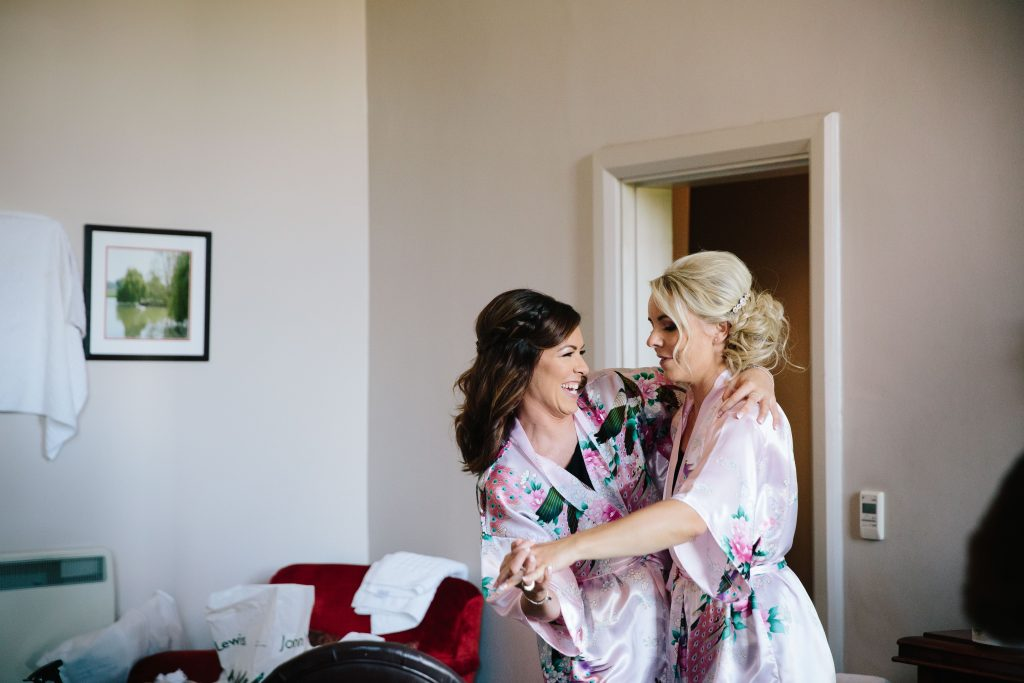 Bridesmaids dancing as they get ready for the wedding at Walton Hall