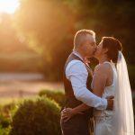 bride & Groom kissing at sunset