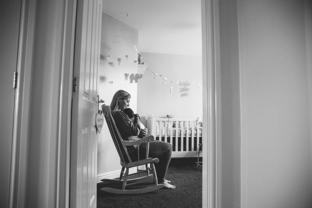 Black & white image of Mum holding baby in the nursery, sitting in a rocking chair