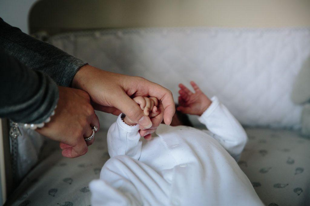 Mum holding hands with her newborn baby son