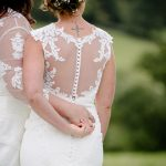 Bride & Bride holding hands from behind