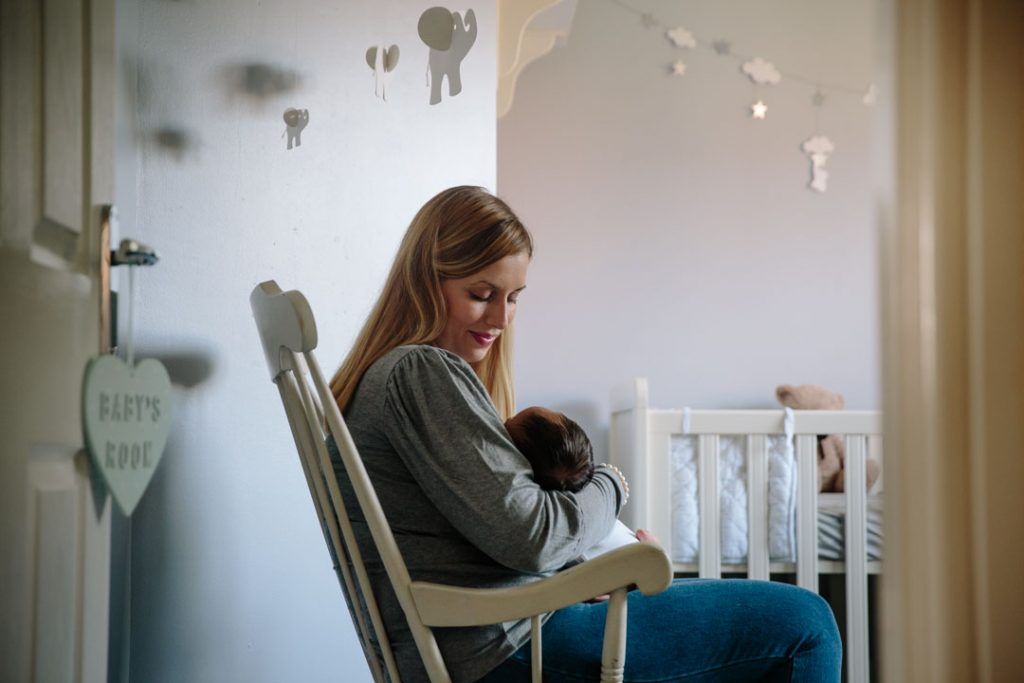 Mum holding baby boy, sitting in rocking chair in the nursery
